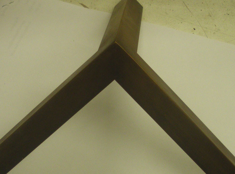 Brass – welded on inside and patinated – not very strong, but neat and with crisp edges